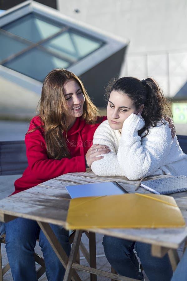 Mulher desesperada do estudante que obtém o apoio de seu melhor amigo que senta-se fora fotos de stock royalty free