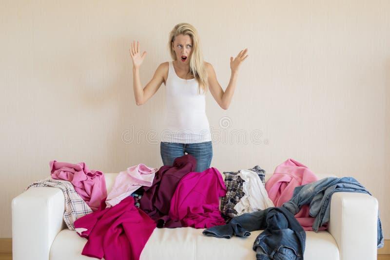 Mulher desesperada que olha a confusão em seu sofá foto de stock
