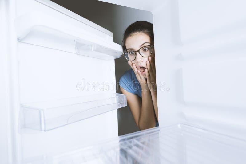 Mulher desesperada que olha em seu refrigerador vazio imagens de stock royalty free
