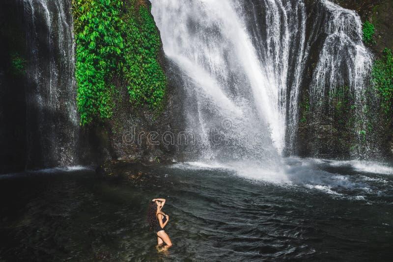 Mulher desfrutando em lagoa de enorme cascata tropical Banyumala em Bali imagem de stock
