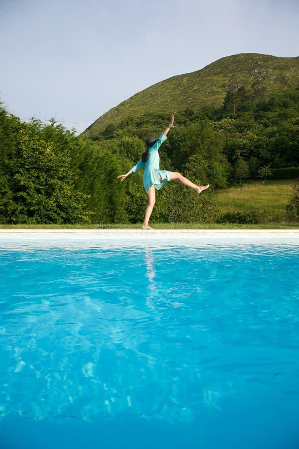A mulher desliza na beira da piscina fotografia de stock