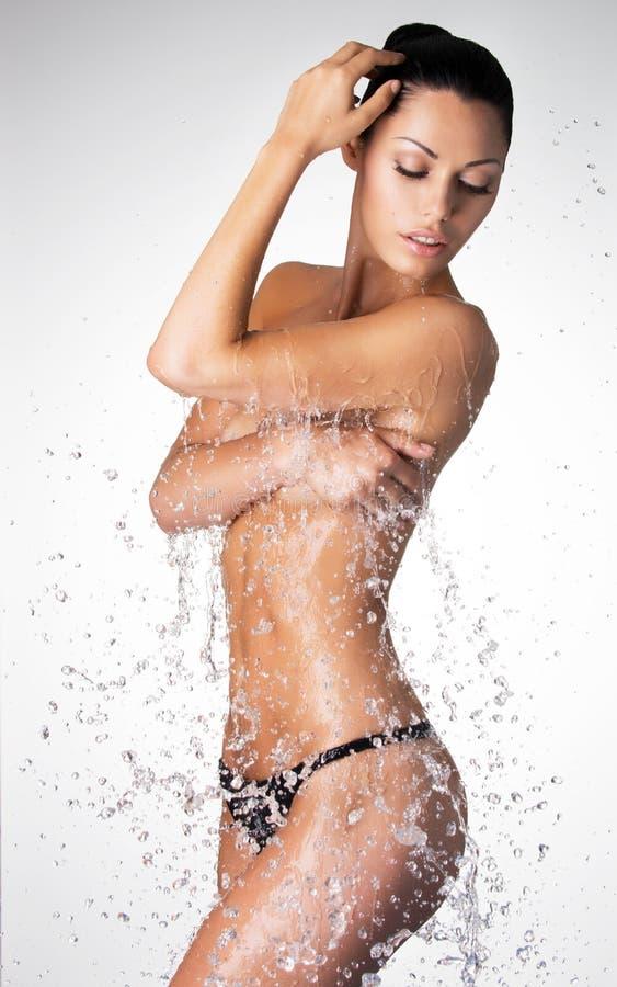 A mulher despida bonita com corpo molhado e espirra da água fotografia de stock royalty free