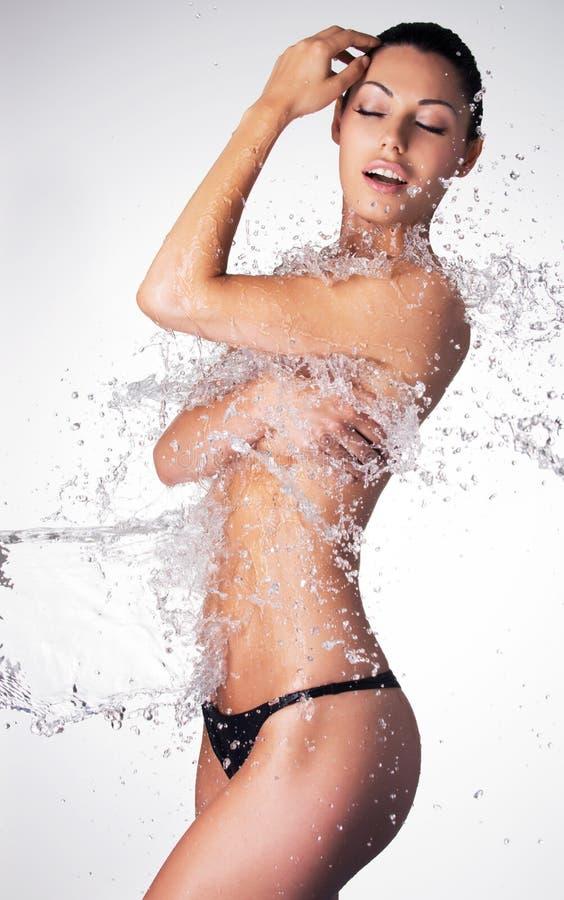 A mulher despida bonita com corpo molhado e espirra da água foto de stock royalty free
