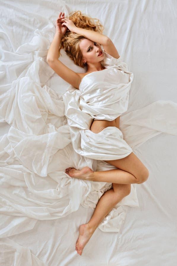 Mulher despida bonita na cama branca fotos de stock royalty free