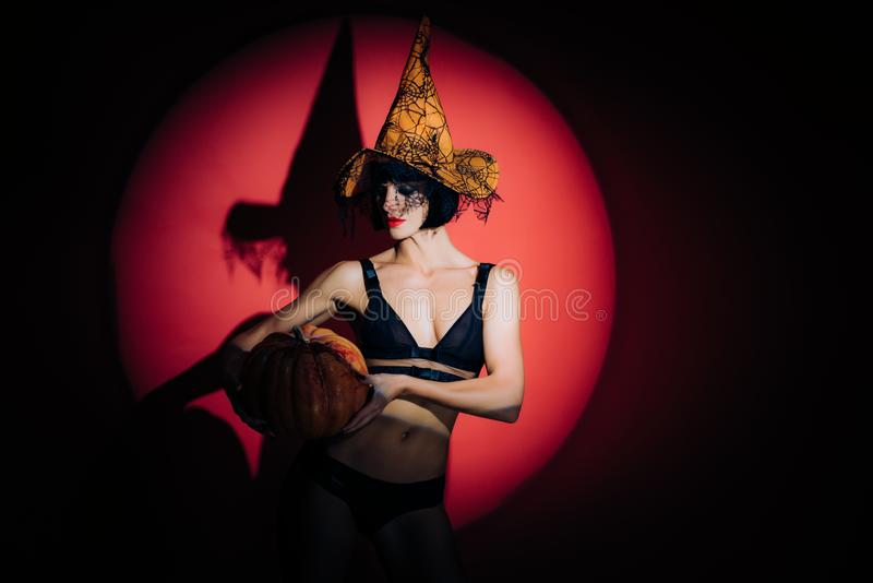 Mulher despida bonita no chapéu das bruxas e no traje do Dia das Bruxas Retrato sensual da mulher de Dia das Bruxas Encantador el foto de stock royalty free