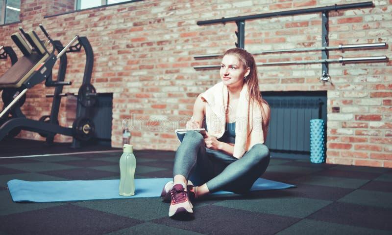 A mulher desportiva alegre senta-se e descansando em uma esteira de formação e escreve-se para baixo os planos de formação futuro imagens de stock