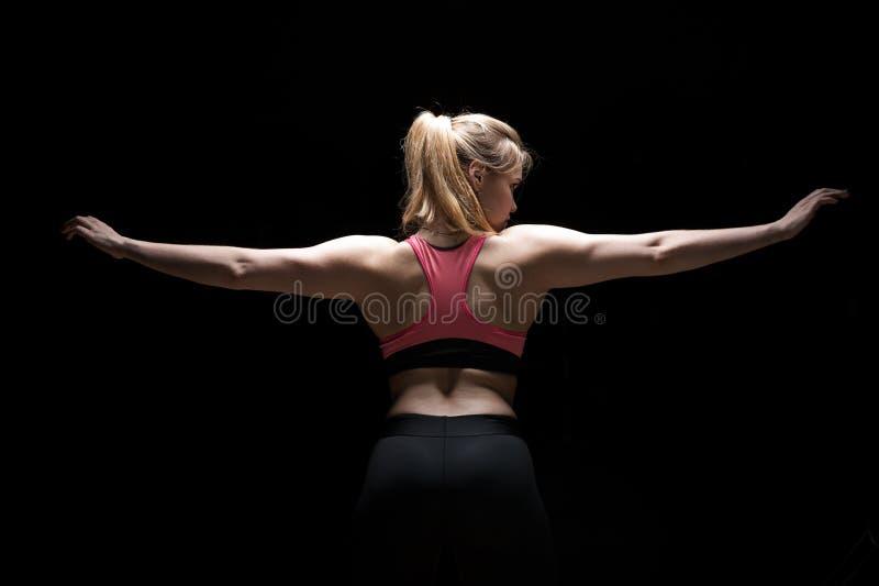 Mulher desportiva apta que mostra seus para trás músculos fotografia de stock