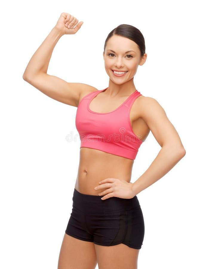 Mulher desportiva asiática que dobra seu bíceps fotos de stock