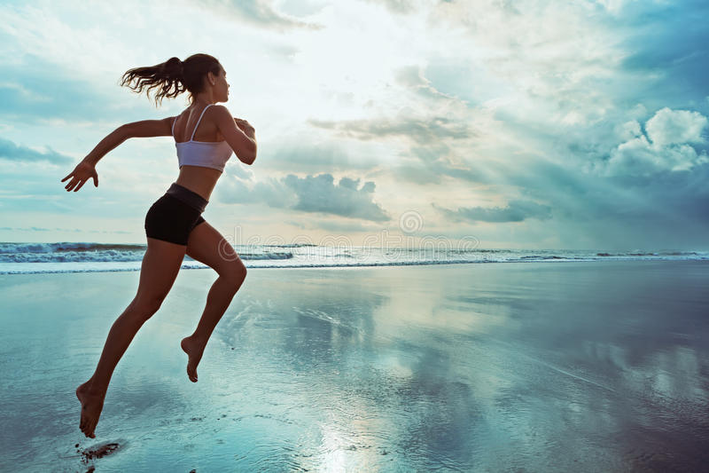 A mulher desportiva ativa corre ao longo da praia do oceano do por do sol Ostenta o fundo fotos de stock royalty free