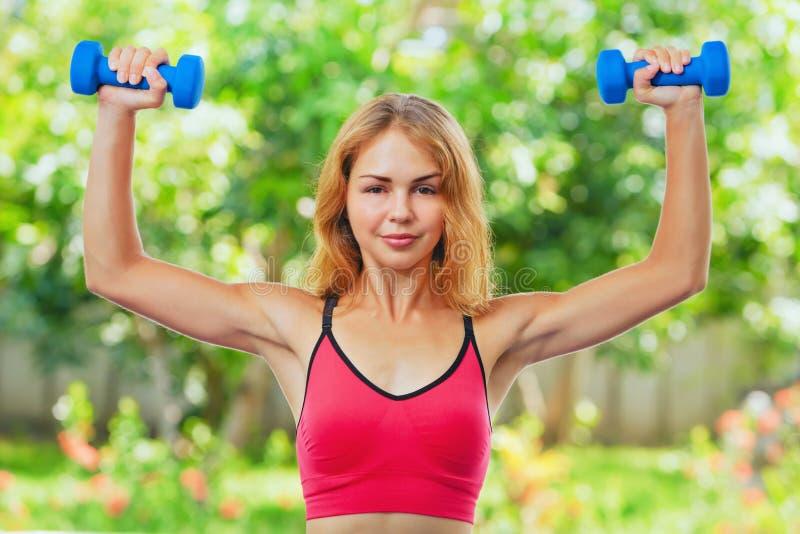 A mulher desportiva ativa que faz a manhã exercita com pesos em casa imagem de stock royalty free