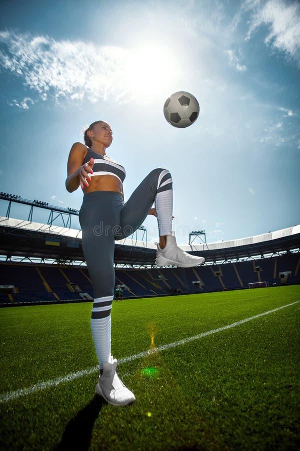 Mulher desportiva atlética no sportswear com a bola de futebol no estádio foto de stock royalty free