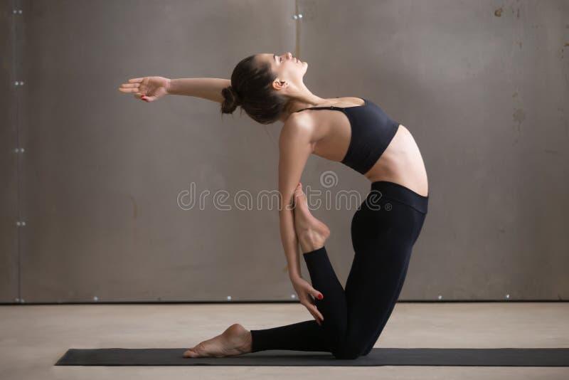 Mulher desportiva atrativa nova na pose de Ustrasana, CCB cinzento do estúdio foto de stock royalty free