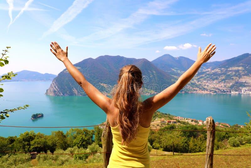 Mulher desportiva bem sucedida que aumenta os braços para o céu azul e o lago bonitos Atleta fêmea que comemora o sucesso e os ob imagem de stock royalty free