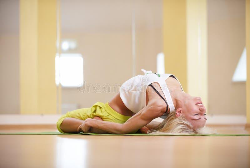 A mulher desportiva bonita do iogue do ajuste pratica o asana Matsyasana da ioga - pesque a pose na sala da aptidão fotografia de stock