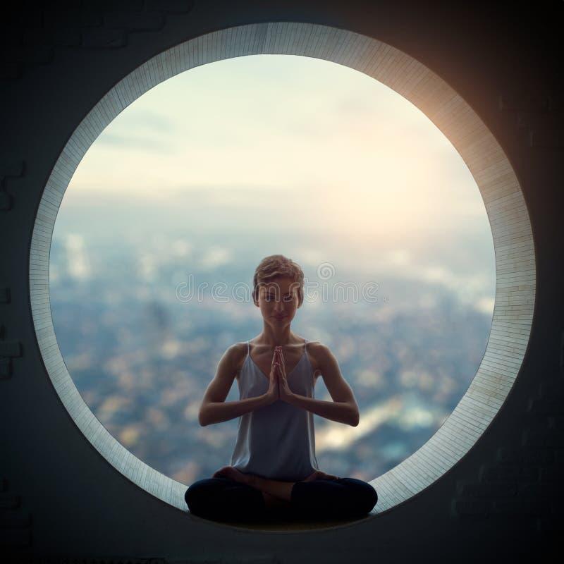 A mulher desportiva bonita do iogue do ajuste pratica o asana Padmasana da ioga - a pose de Lotus em uma janela redonda foto de stock