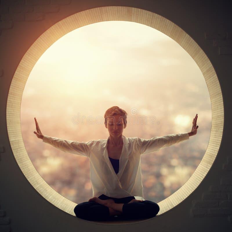 A mulher desportiva bonita do iogue do ajuste pratica o asana Padmasana da ioga - a pose de Lotus em uma janela redonda imagens de stock