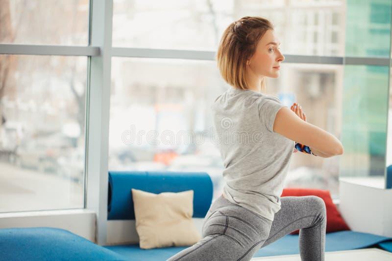 A mulher desportiva bonita do yogini do ajuste pratica o asana Virabhadrasana 2 da ioga - a pose 2 do guerreiro foto de stock