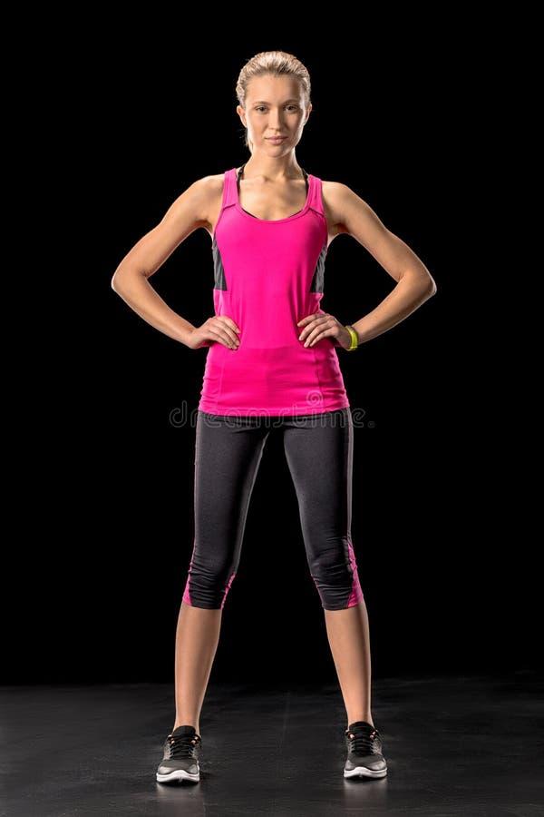 Mulher desportiva bonita no sportswear que levanta com mãos na cintura foto de stock