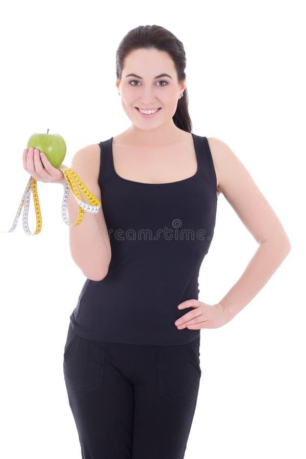 Mulher desportiva bonita nova com maçã e o isola de medição da fita foto de stock royalty free
