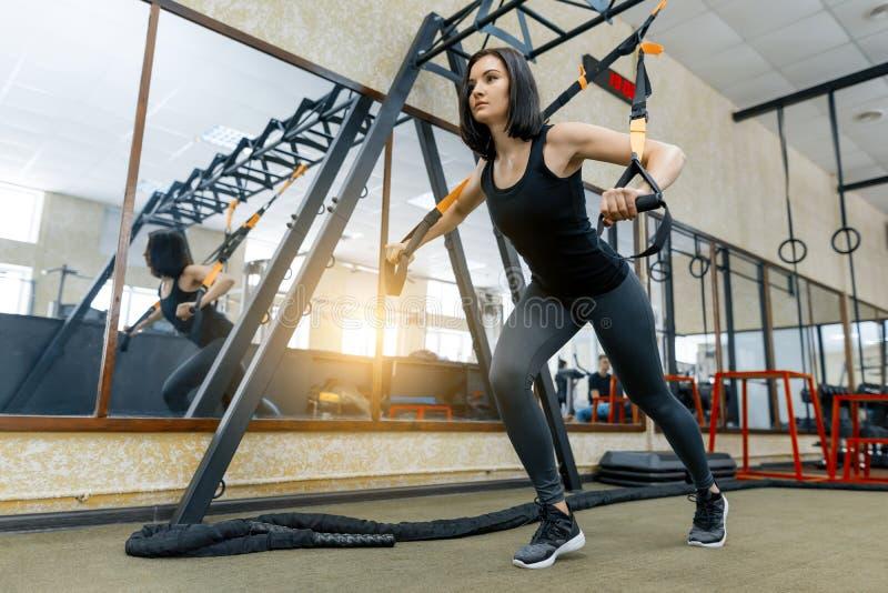 Mulher desportiva bonita nova que exercita no sistema das correias da aptidão no gym Aptidão, esporte, treinamento, e conceito sa foto de stock