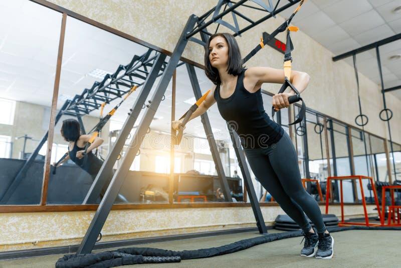 Mulher desportiva bonita nova que exercita no sistema das correias da aptidão no gym Aptidão, esporte, treinamento, e conceito sa fotos de stock