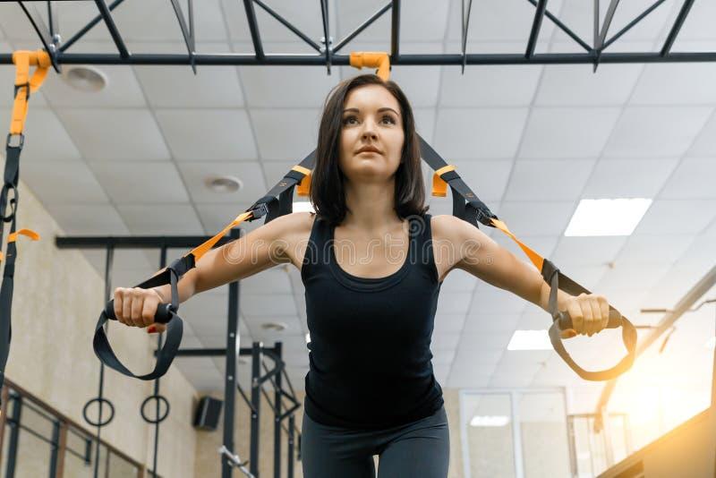 Mulher desportiva bonita nova que exercita no sistema das correias da aptidão no gym Aptidão, esporte, treinamento, e conceito sa imagem de stock royalty free