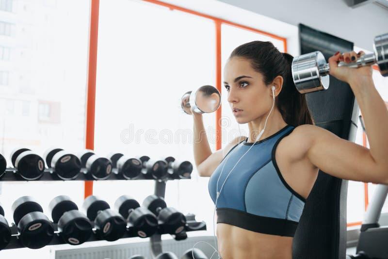 Mulher desportiva bonita que faz o exercício da aptidão do poder no gym do esporte fotografia de stock