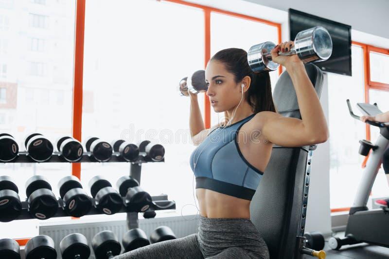 Mulher desportiva bonita que faz o exercício da aptidão do poder no gym do esporte imagem de stock
