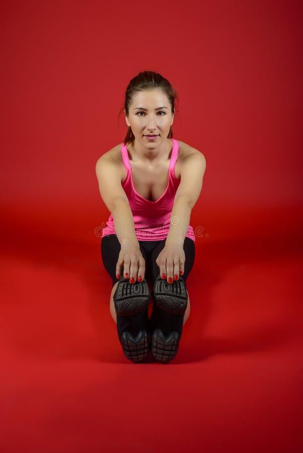 Mulher desportiva bonita que faz o exercício no assoalho imagens de stock