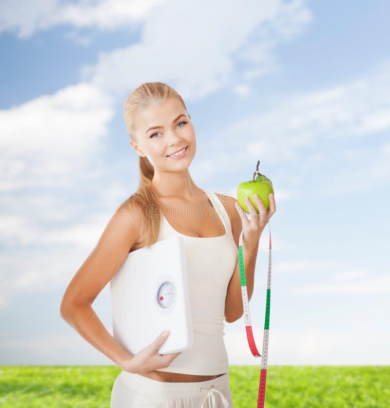 Mulher desportiva com escala, maçã e a fita de medição fotografia de stock royalty free