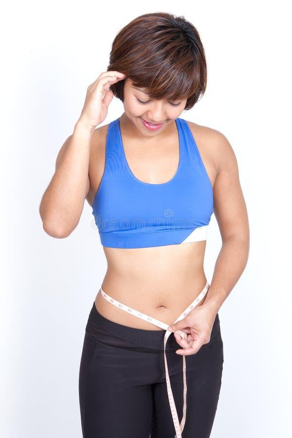 Mulher desportiva com a fita de medição em torno do quadril. fotos de stock