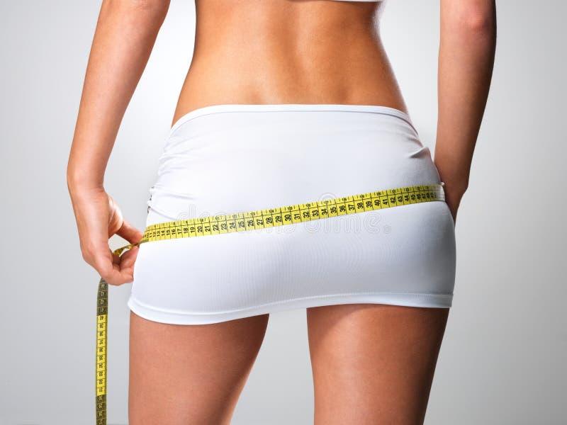 Mulher desportiva com os quadris de medição do corpo magro fotografia de stock royalty free