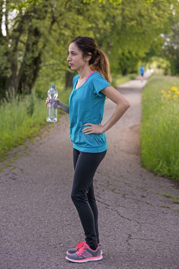 Mulher desportiva com uma garrafa da água durante uma ruptura foto de stock royalty free