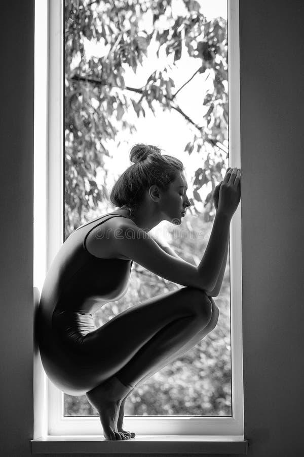 Mulher desportiva consideravelmente 'sexy' na janela fotografia de stock