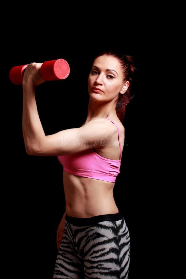 Mulher desportiva da aptidão com o bíceps da mostra do peso em um isolat preto foto de stock