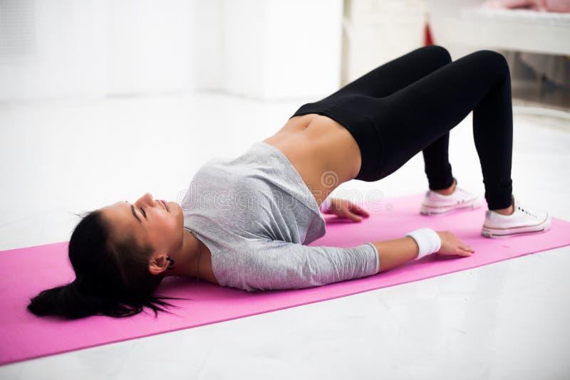 Mulher desportiva da pose da ponte que faz aquecendo o exercício imagens de stock