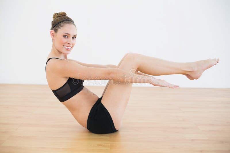 A mulher desportiva de sorriso bonita que senta-se no assoalho que faz esportes exercita fotos de stock royalty free