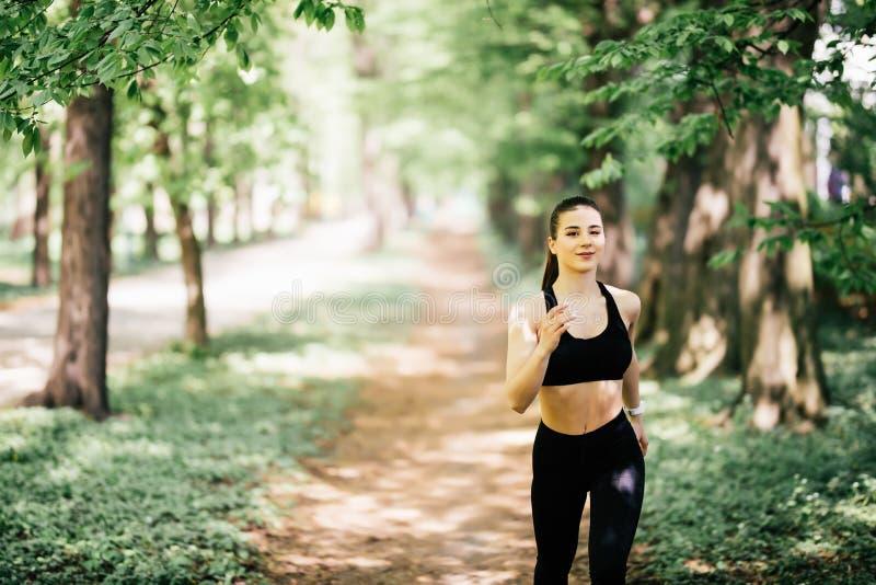 Mulher desportiva de sorriso dos jovens que corre no parque Menina da aptidão que movimenta-se no parque fotos de stock royalty free