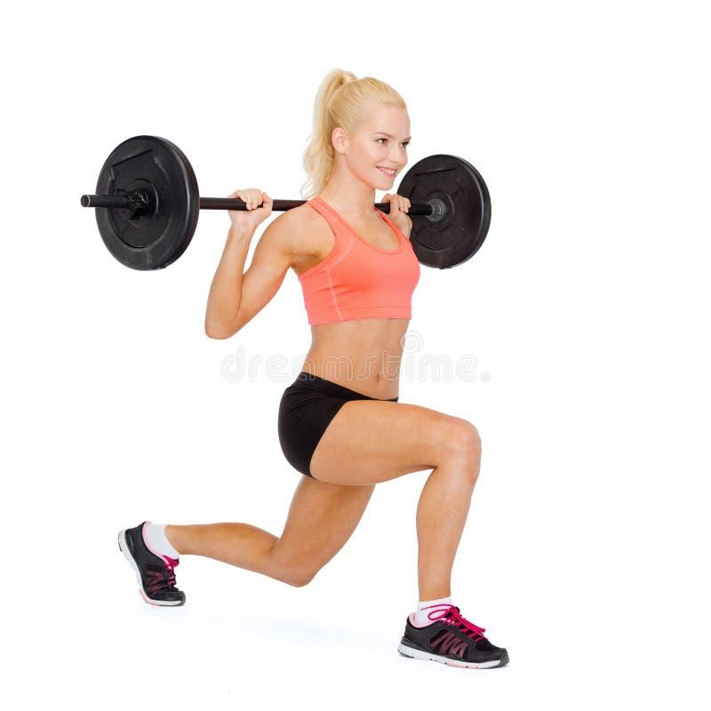 Mulher desportiva de sorriso que exercita com barbell imagens de stock royalty free