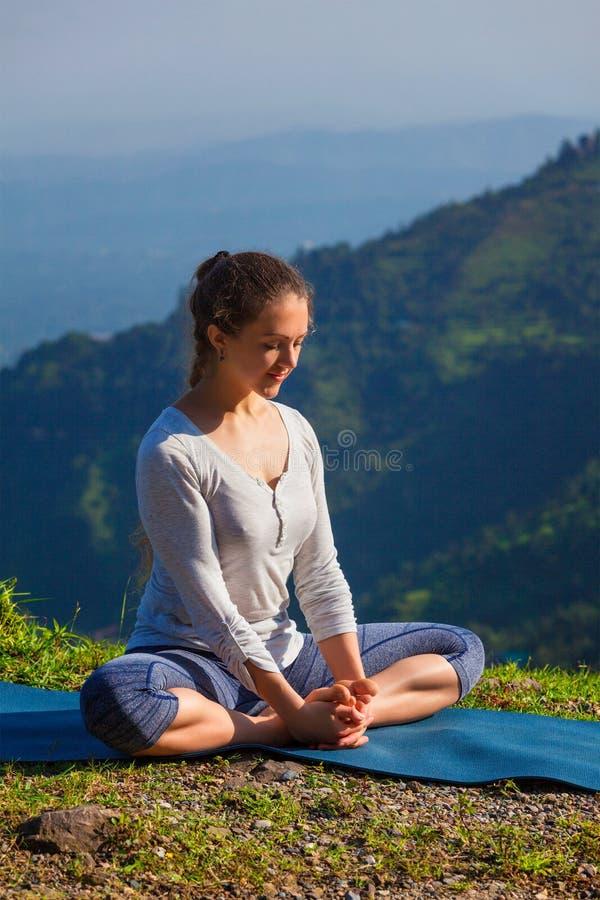 A mulher desportiva do ajuste pratica o asana Baddha Konasana da ioga fora imagens de stock
