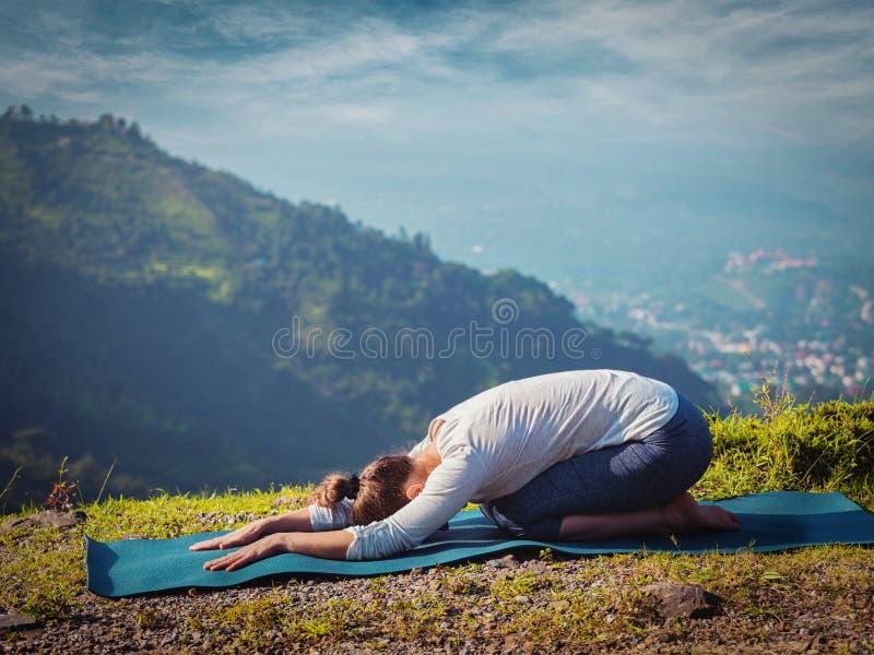 A mulher desportiva do ajuste pratica o asana Balasana da ioga imagens de stock