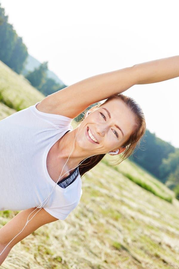 A mulher desportiva e ativa faz a ginástica aeróbica imagens de stock