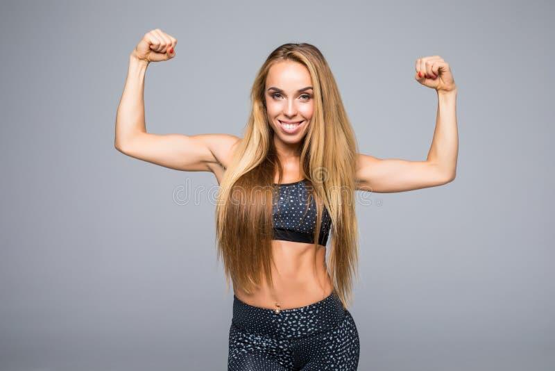 A mulher desportiva está mostrando-lhe as mãos fortes no fundo cinzento imagens de stock