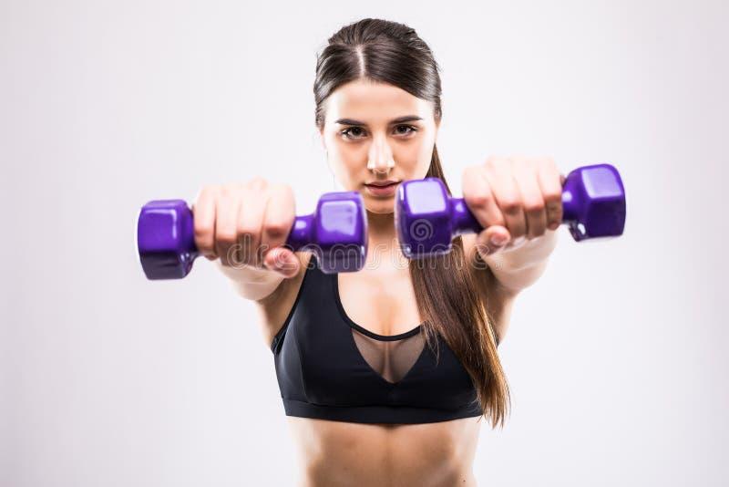 A mulher desportiva faz os exercícios com pesos no fundo branco Jovem mulher no sportswear no fundo branco Força e mo foto de stock