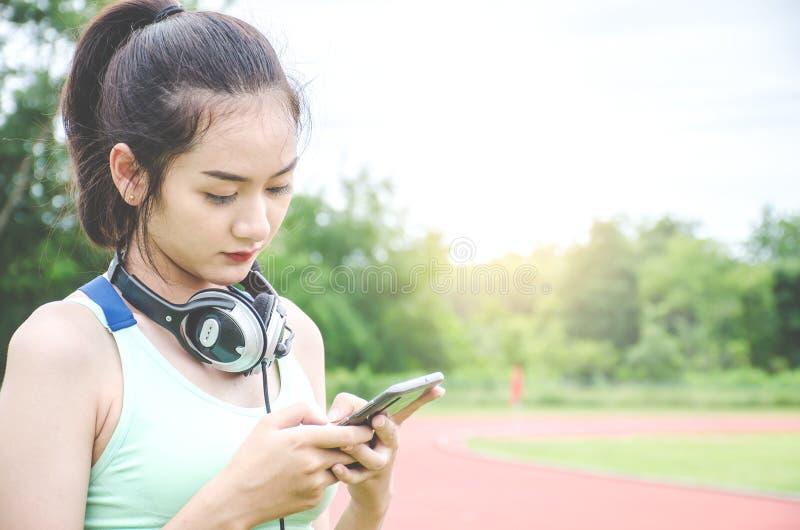 Mulher desportiva feliz com fones de ouvido, está procurando a música que usa em linha sua tabuleta digital após a escada rolante fotografia de stock