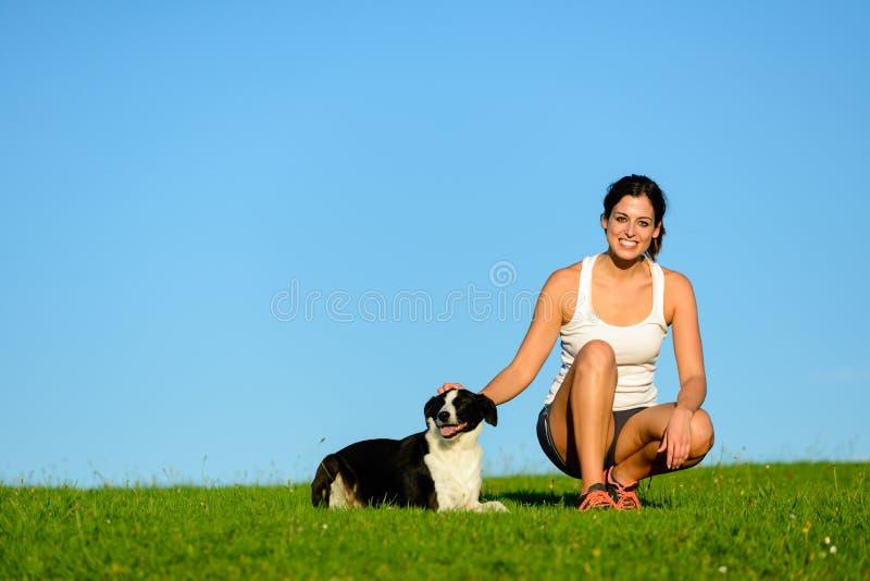 Mulher desportiva feliz que toma um resto de exercício com seu cão foto de stock royalty free