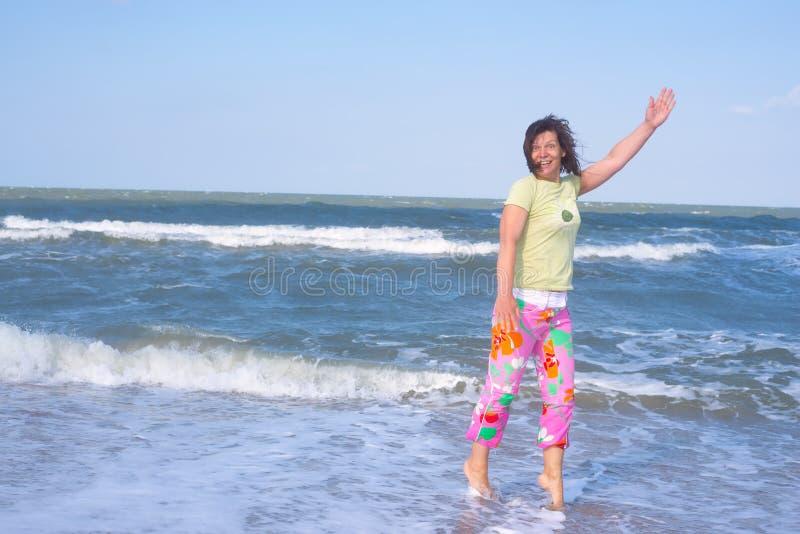 A mulher desportiva louca está rindo expressively na praia foto de stock royalty free