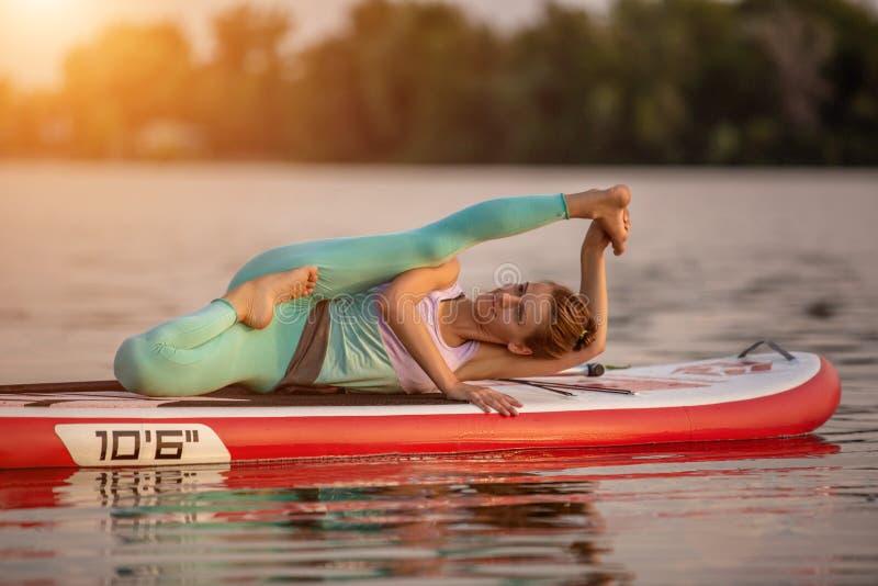 Mulher desportiva na posição da ioga sobre o paddleboard, fazendo a ioga na placa do sup, o exercício para a flexibilidade e o es imagem de stock royalty free