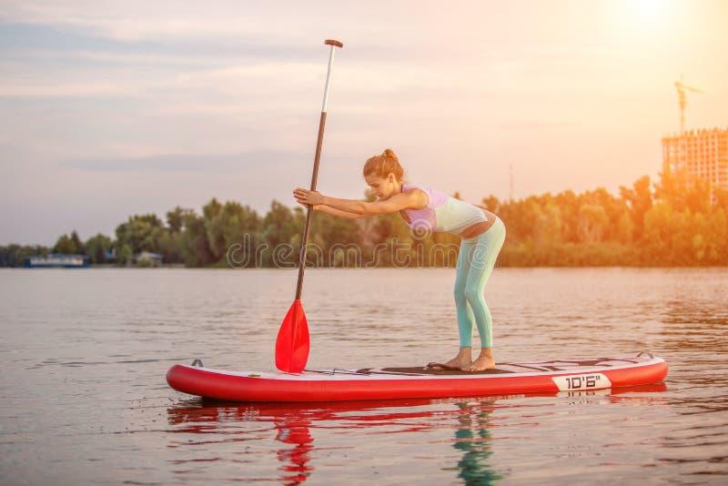 Mulher desportiva na posição da ioga sobre o paddleboard, fazendo a ioga na placa do sup, o exercício para a flexibilidade e o es fotos de stock royalty free