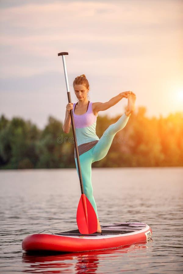 Mulher desportiva na posição da ioga sobre o paddleboard, fazendo a ioga na placa do sup, o exercício para a flexibilidade e o es fotografia de stock